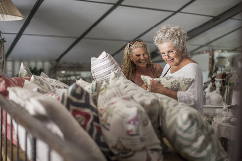 Two women shopping for pillows in vintage store - ZEF008778