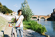 Italy, Verona, young woman with bicycle by the riverside - GIOF001220