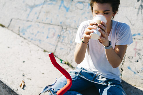 Young woman drinking coffee from disposable cup - GIOF001226