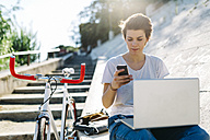Young woman with bicycle sitting outdoors using laptop and cell phone - GIOF001229