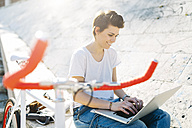 Young woman with bicycle sitting outdoors using laptop - GIOF001232