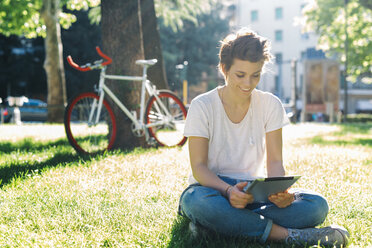 Smiling young woman sitting on meadow using digital tablet - GIOF001238