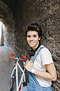 Portrait of smiling young woman with bicycle at stone wall - GIOF001247