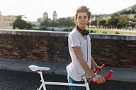 Young woman pushing bicycle on bridge - GIOF001250