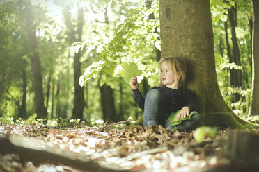 Girl in forest examining leaves - SBOF000153