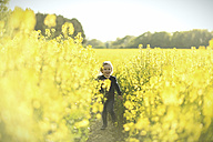 Happy girl running in canola field - SBOF000165