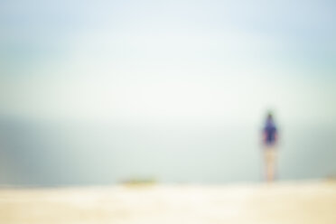 Back view of woman standing on the beach looking to the sea - CMF000497