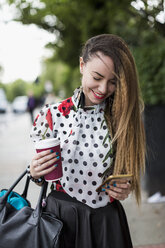Portrait of smiling woman with coffee to go looking at her smartphone - MAUF000662