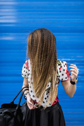 Braided hair of stilished young woman in front of blue roller shutter - MAUF000665