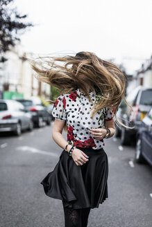 Stylished young woman shaking her hair - MAUF000668