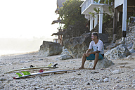 Indonesia, Bali, surfer sitting on the beach - KNTF000377