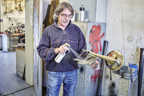 Instrument maker using spray can for trumpet - DIKF000187