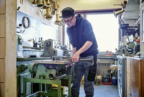 Instrument maker making trumpet in workshop - DIKF000190