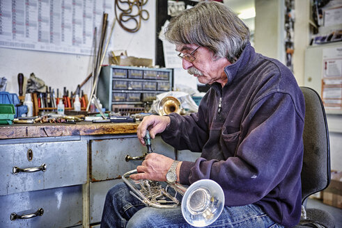 Instrument maker repairing trumpet in workshop - DIKF000202