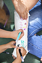 Little girls painting her mother's plaster arm - ERLF000182