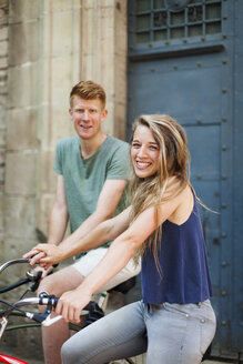 Portrait of laughing woman with bicycle holding hand with her boyfriend in the background - VABF000597