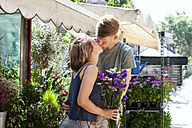 Kissing couple in front of flower stall - VABF000603