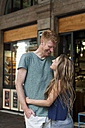 Happy couple standing in front of a coffee shop looking at each other - VABF000609