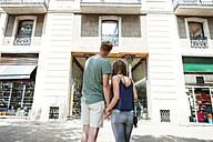 Spain, Barcelon, back view of couple holding hands in front of a building - VABF000618