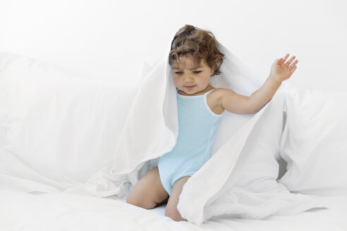 Baby girl kneeling on a white bed playing with a towel - LITF000380
