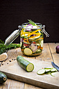 Glass of pickled courgette and bell pepper, preparation with different spices - LVF004981