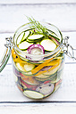 Glass of pickled courgette and bell pepper, white wood - LVF004987