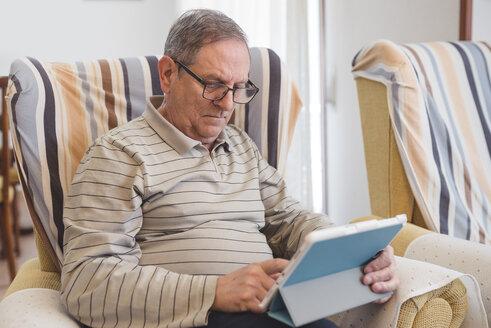 Senior man at home using digital tablet - EPF000111
