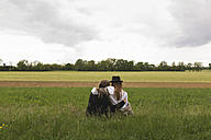 Back view of two friends sitting on a meadow at countryside - BOYF000420