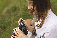 Woman with an old camera on a meadow - BOYF000432