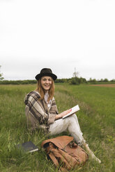 Portrait of smiling young woman sitting on a meadow with a book - BOYF000435