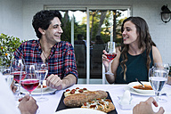 Man and woman having fun and drinking lambrusco wine during a summer dinner - ABZF000731