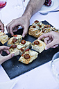 Hands taking a piece of focaccia during a summer dinner - ABZF000734