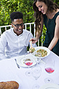 Woman serving tabbouleh to her guest during a summer dinner - ABZF000737
