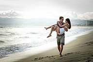 Man carrying his girlfriend on the beach - ABAF002053