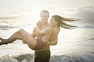 Man carrying his girlfriend at seafront - ABAF002056