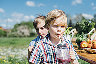 Two boys outdoors drinking from jars - MJF001902