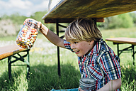 Boy under beer table holding glass with jelly beans - MJF001920