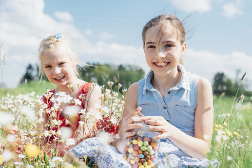 Two happy girls in meadow with glass with jelly beans - MJF001923