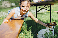 Portrait of smiling girl with dog lying on wooden bench - MJF001944