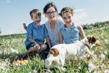 Happy mother and two children with dog in meadow - MJF001956