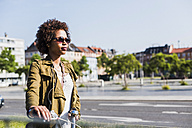 Portrait of young woman wearing sunglasses pushing bicycle - UUF007731