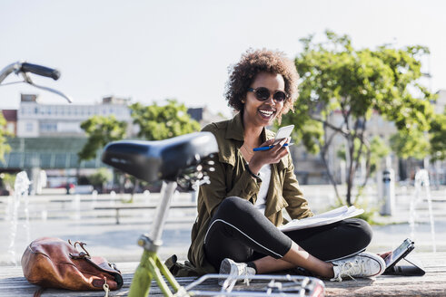 Portrait of young woman sitting on a  bench using smartphone and digital tablet - UUF007740
