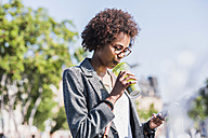 Woman drinking beverage while looking at her smartphone - UUF007752