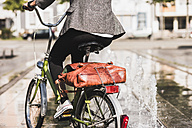 Back view of woman riding bicycle, partial view - UUF007755