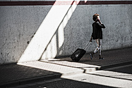 Walking businesswoman with baggage telephoning with smartphone - UUF007758