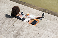 Young woman sitting on stairs eating an apple while looking at her smartphone - UUF007764