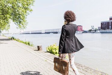 Germany, Mannheim, back view of  young businesswoman with briefcase and coffee to go walking at riverside - UUF007770