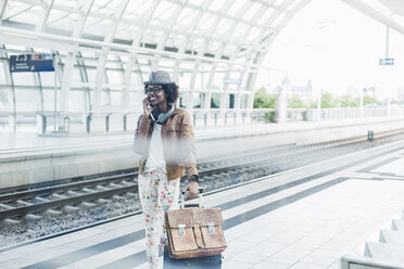 Young woman telephoning with smartphone while waiting at platform - UUF007776