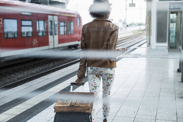 Back view of young woman with trolley bag and briefcase at platform - UUF007779