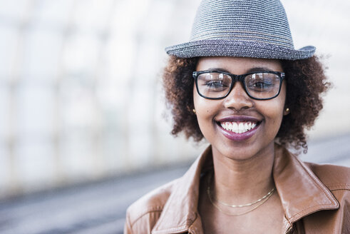 Portrait of smiling young woman wearing hat and glasses - UUF007782